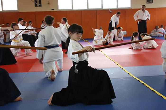 Fille sur tatami avec sabre en bois
